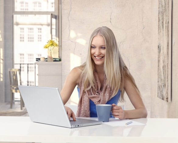 Happy young blonde casual caucasian woman working with laptop co